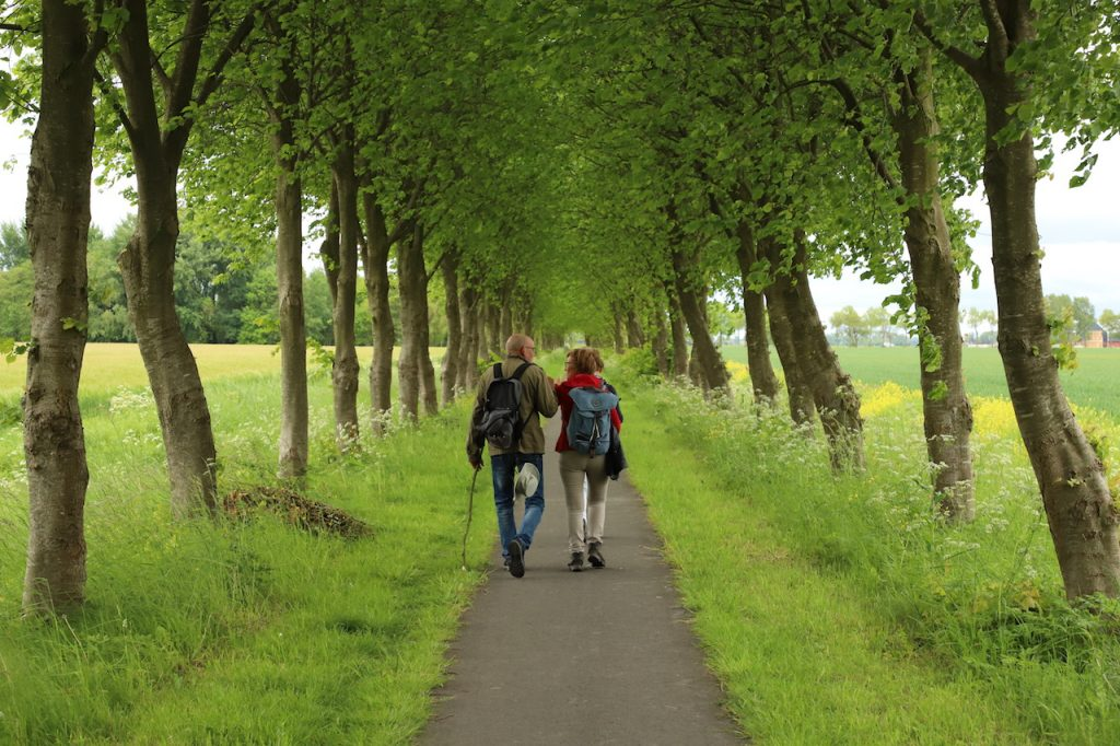 Twee wandelaars van het Groninger Borgenpad bij het borgterrein van Starkenborgh